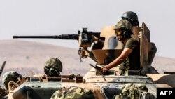 Tentara Turki duduk di atas tank menuju Suriah dari kota perbatasan Karkamis di Gaziantep (27/8). (AFP/Bulent Kilic)