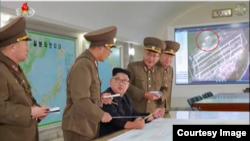 김정은 국무위원장 왼편 화면에 괌 앤더슨 공군기지 위성사진이 떠 있다. 원안 부분으로 이 사진이 2011년 찍힌 사실을 알 수 있다. 출처=조선중앙TV