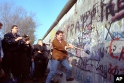 An unidentified West Berliner swings a sledgehammer, trying to destroy the Berlin Wall near Potsdamer Platz, on November 12, 1989, where a new passage was opened nearby. (AP Photo/John Gaps III)