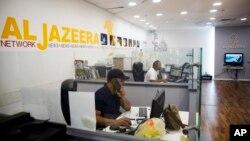 Employees sit in Al-Jazeera news network offices in Jerusalem, Aug. 8, 2017.