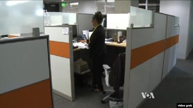 Cô Michelle Baxter đứng làm việc ở bàn giấy