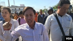 Vorn Pov, director of the development organization IDEA and a worker representative, center, shouted at authorities on Sunday as they sought to disperse the mourners, January 3rd, 2016. (Hul Reaksmey/VOA Khmer)