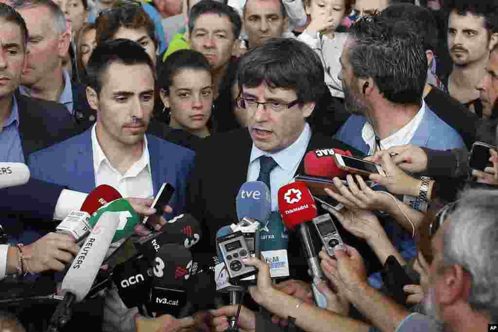 El presidente de Cataluña, Carles Puigdemont, habla a los medios de comunicación en un centro deportivo, asignado como mesa de votación por el gobierno catalán en Sant Julià de Ramis, cerca de Girona, el 1 de octubre de 2017.