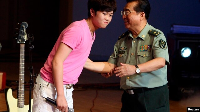 Li Tianyi and his father Li Shuangjiang, a general of the Chinese People's Liberation Army who gained fame singing revolutionary songs, at Li Tianyi's solo concert in Beijing, August 19, 2011.