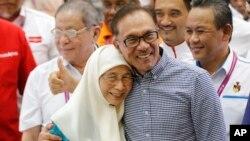 Politisi Malaysia Anwar Ibrahim (kanan) merayakan kemenangan pemilu parlemen di Port Dickson, kota di pesisir selatan Malaysia, Sabtu, 13 Oktober 2018. (Foto:AP)