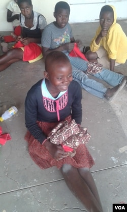 Zimbabwean girls smile after making their own sanitary pads. They can hardly get money to buys pads. (VOA)