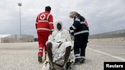 Des éléments de la Croix rouge assistent un migrant qui a débarqué au port scilien d'Augusta, Italy, 31 mai 2013