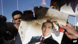 Des protestataires brûlent une photo de l'ancien président tunisien Zine el Abidine Ben Ali lors d'une manifestation à Tunis, le 24 janvier 2011.