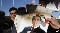 In this January 24, 2011 picture, protestors burn a photo of former Tunisian President Zine El Abidine Ben Ali during a demonstration against holdovers from Ben Ali's regime in the interim government in Tunis, Tunisia.