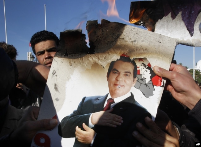 In this Jan. 24, 2011 picture, protesters burn a photo of former Tunisian President Zine El-Abidine Ben Ali during a demonstration against holdovers from Ben Ali's regime in the interim government in Tunis, Tunisia.