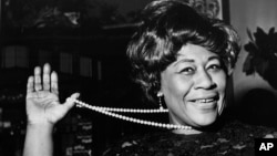 "FILE - In this Feb. 22, 1968 file photo, American jazz singer Ella Fitzgerald swings her necklace as she arrives at the Carlton Theatre in London, England. The National Portrait Gallery is putting up a photograph of Fitzgerald, often referred to as ""The First Lady of Song."" The portrait is on view beginning Thursday, April 13, 2017, ahead of the 100th anniversary of Fitzgerald's birth. Fitzgerald, who died in 1996 at the age of 79, would have celebrated her 100th birthday April 25."