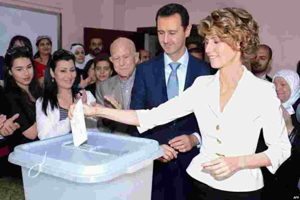 A photo from the official Facebook page of Syria's First Lady Asma al-Assad shows Syrian President Bashar al-Assad watches on as she votes at a polling station in Maliki, Damascus, June 3, 2014.