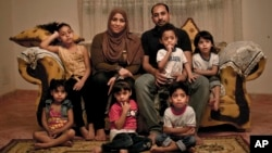 Egyptian father Youssef Shaman Gumaa, center right, and his wife Sarah Hassan Shehata, pose for a photograph with their 4 year-old quintuplets and their 7 year-old sister, top left, at their home during the holy month of Ramadan, in Madinet el-Salam on the outskirts of Cairo, Egypt, May 31, 2017.