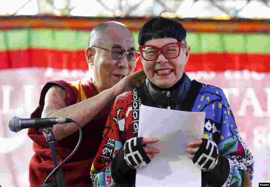 A host reacts on stage as exiled Tibetan spiritual leader the Dalai Lama sneaks up behind her during his first public appearance on his current visit to Australia, at a school in Katoomba, west of Sydney.