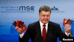 Presiden Ukraina Petro Poroshenko memegang paspor Rusia untuk membuktikan kehadiran pasukan Rusia di Ukraina ketika berbicara dalam Konferensi Keamanan Munich ke-51di Hotel 'Bayerischer Hof' di Munich 7 Februari 2015. (REUTERS/Michael Dalder)