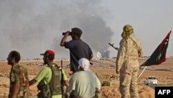 Повстанці поблизу північної брами міста Бані Валід. Над містом підіймаються клуби диму.