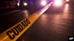 """FILE - Police tape that reads in Spanish """"Caution"""" marks off a crime scene in Mexico."""