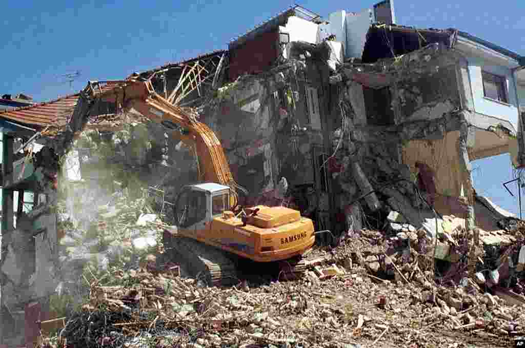 A bulldozer tears down a damaged building as part of clean up following the earthquake in the Turkish western city of Yalova, September 7, 1999. (AP)