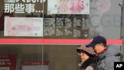 Residents walk past board highlighting the security markers on the latest Yuan note outside a bank in Beijing, China, Nov. 24, 2016.