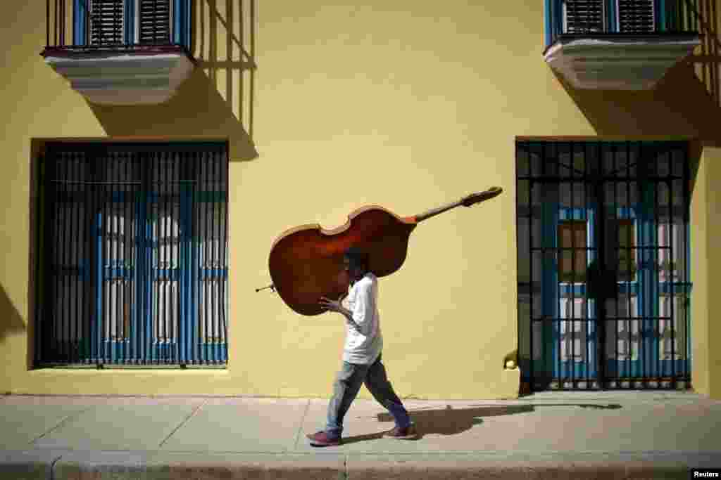 Musician Frilal Ortiz carries a cello in downtown Havana, Cuba.