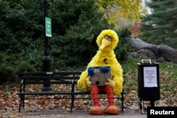 "FILE - A man dressed as the ""Sesame Street"" character Big Bird sits on a bench in New York's Central Park, Nov. 14, 2016. In the localized versions of ""Sesame Street"" to be shown to kids caught up in the Syrian civil war, the characters will have regional names and speak Arabic and Kurdish."