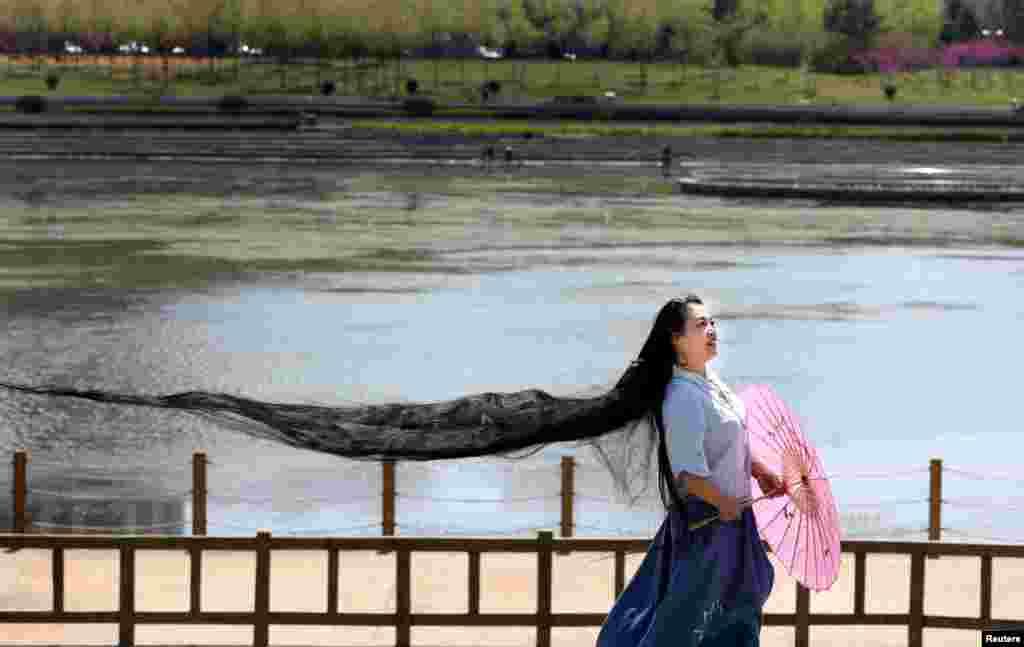 Seorang perempuan berambut panjang berpose di Weihai, Shandong, China.