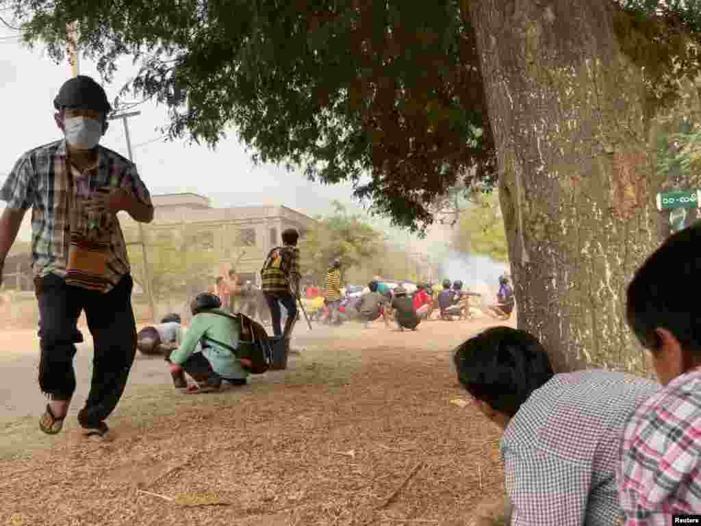 Protesters take cover during clashes with security forces in Monywa, Myanmar March 21, 2021,