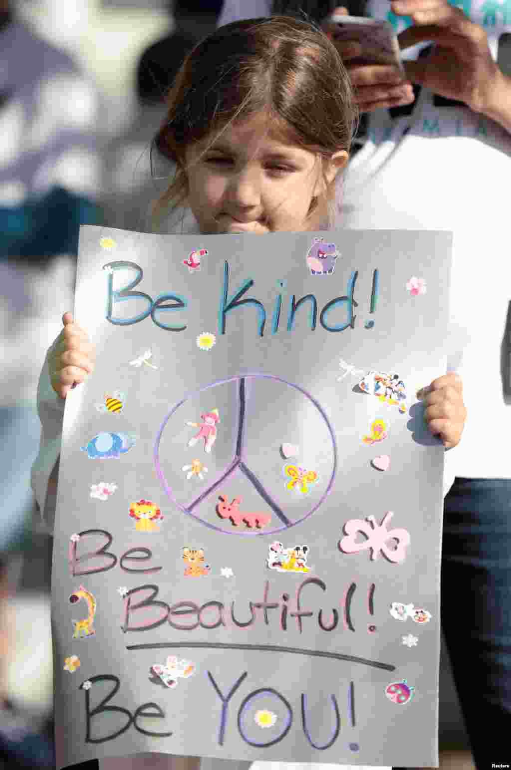 یک دختربچه با در دست داشتن علامت صلح در راهپیمایی اعتراضی موسوم به راهپیمایی برای زندگی در فلوریدا.