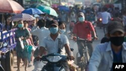 Commuters wearing face masks amid concerns over the spread of the COVID-19 coronavirus make their way on bikes in the Hlaing Tharyar township on the outskirts of Yangon on May 16, 2020. (Photo by Sai Aung Main / AFP)