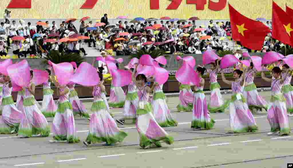 Vietnamese school children perform dances during a military parade in Hanoi, to mark the 70th anniversary of independence from France.