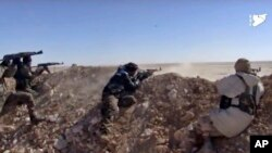 FILE - This frame grab from a video provided by the Syria Democratic Forces shows fighters from the SDF opening fire on an Islamic State group's position, in Raqqa's eastern countryside, Syria, March 6, 2017.