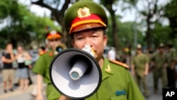 A Vietnamese police officer uses a speaker to order pedestrians including journalists to leave a closed area near the Chinese Embassy in Hanoi, Vietnam, May 18, 2014.