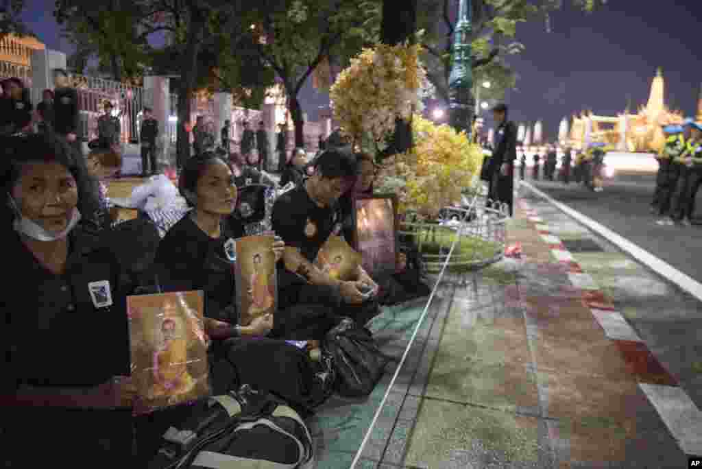 Thai mourners sit with portraits of the late King Bhumibol Adulyadej near Grand Palace to take part in the Royal Cremation ceremony in Bangkok, Thailand, Wednesday, Oct. 25, 2017.  (AP Photo/Kittinun Rodsupan)