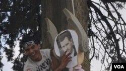 Seorang demonstran anti pemerintah Suriah menggantung patung Presiden Bashar al-Assad (foto: dok).