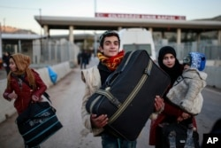 FILE - Members of a Syrian family carry their belongings after they crossed into Turkey at the Cilvegozu border gate with Syria, near Hatay, southeastern Turkey, Dec, 18, 2016.
