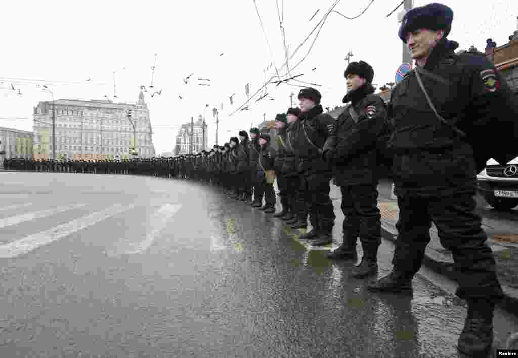 Riot police stand guard during a march by opposition supporters to commemorate Kremlin critic Boris Nemtsov, who was shot dead on Friday night, in Moscow, March 1, 2015.