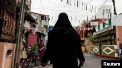 ایک مسلمان خاتون برقعہ پہنے کولمبو میں ایک مسیحی عبادت گاہ سینٹ انتھونی کے قریب سے گزر رہی ہے۔ 29 اپریل 2019