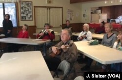 Steve Winget, center, and other seniors at the San Jose (Calif.) Ukulele Club's 2016 Christmas Jam follow the lyrics on a screen at the front of the room.