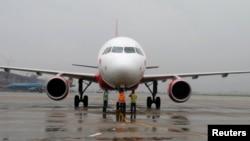 Ground staff check VietJet A320 airplane before departure for Bangkok, Noi Bai international airport, Hanoi.