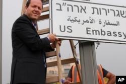 En esta foto publicada por la Municipalidad de Jerusalén, el alcalde de Jerusalén, Nir Barkat, posa con una nueva señal de tráfico en la nueva Embajada de EE.UU. en Jerusalén, Israel, el 7 de mayo de 2018.