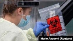 Seorang tenaga kesehatan memberikan paket alat tes Covid-19 mandiri di Stadion Rose Bowl, di tengah pandemi virus corona (Covid-19) di Pasadena, California, 8 April 2020. (Foto: Reuters)