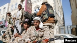 FILE - Houthi fighters ride in a truck while patrolling a street in Sanaa, Yemen, Jan. 21, 2015.