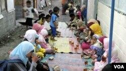 Anak-anak dan perempuan di tempat hunian sementara Dongkelsari berbuka puasa dengan menu sederhana teh manis dan nasi bungkus, Senin (29/8).