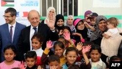 """Le ministre des Affaires étrangères français Jean-Yves Le Drian (2e-G) avec des réfugiés syriens du camp d'Azraq participant au projet d'ONU Femmes """"Oasis pour les femmes et les filles."""""""