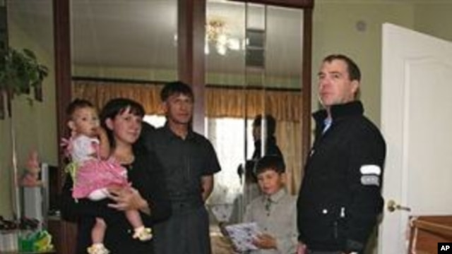 Russian President Dmitry Medvedev, right, visits an unidentified Russian family in the town of Yuzhnokurilsk, at the Pacific Island of Kunashir, Russia, 01 Nov 2010