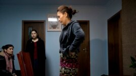 Guzaili Nu'er, wife of Ilham Tohti, right, pauses next to her husband's students at her house in Beijing, Jan. 16, 2014.