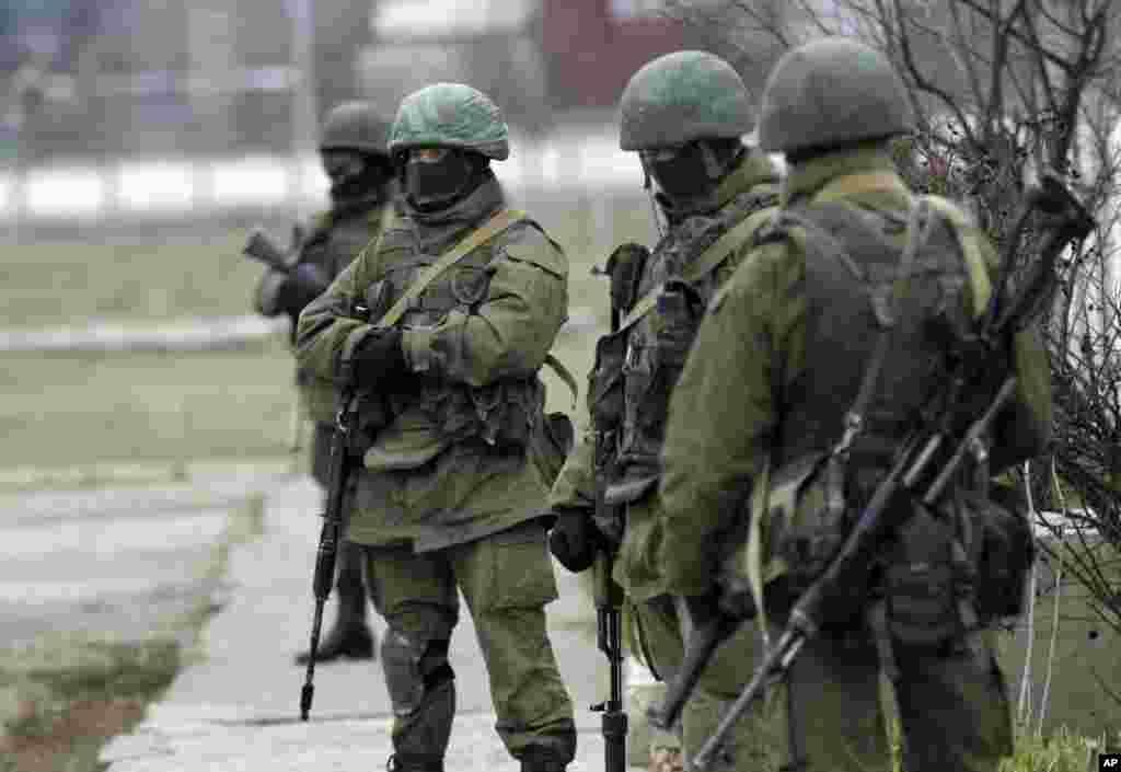 Unidentified gunmen guard Ukraine's infantry base in Privolnoye, Ukraine, March 2, 2014.