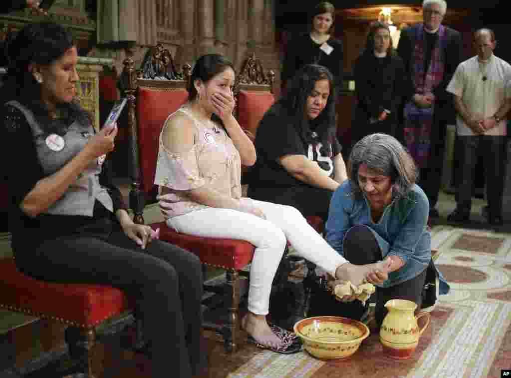 Mientras Jeanette Vizguerra, izquierda, y Myrna Lazcano, tercera desde la izquierda, observan, Aura Hernández, segunda desde la izquierda, se emociona cuando Sunita Viswanath se lava los pies durante un servicio en la Cuarta Sociedad Universalista en Nueva York, jueves 29 de marzo de 2018 AP Photo / Seth Wenig)