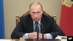 Russian President Vladimir Putin listens during a meeting at the Kremlin in Moscow, Russia, May 27, 2015. Putin said the United States is meddling in FIFA's affairs in an attempt to take the 2018 World Cup away from his country.