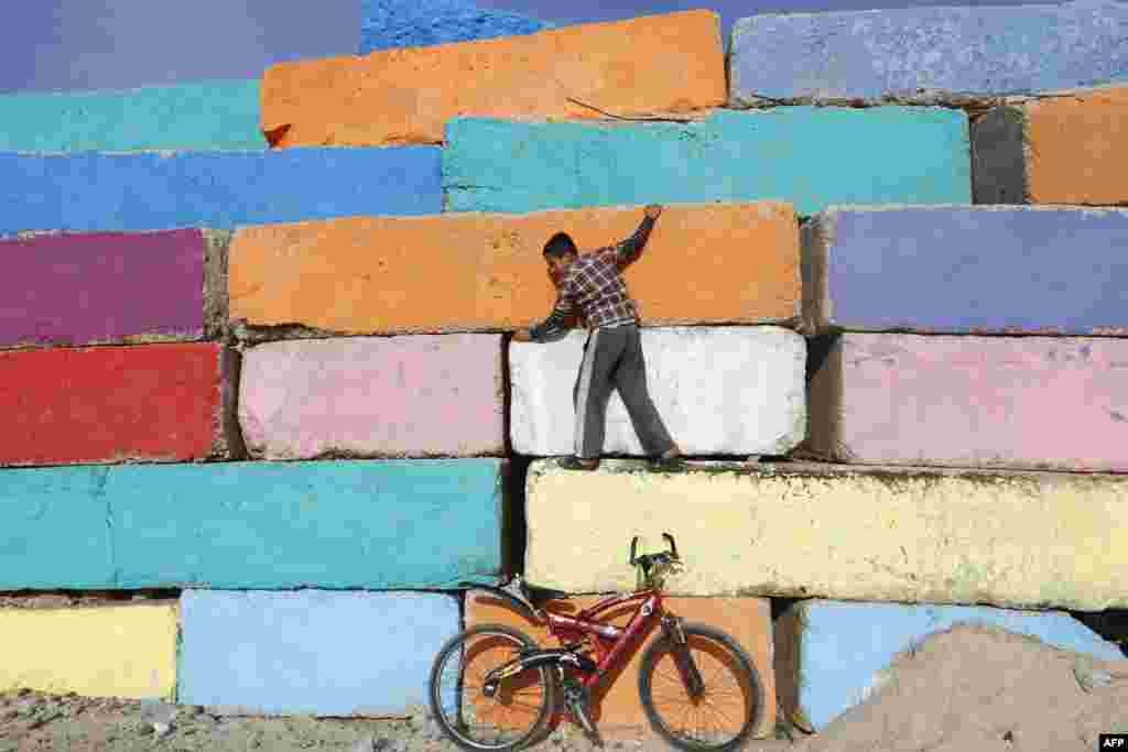 A Palestinian boy climbs a big stone wall, that was painted by local artists at the seaport in Gaza City in an attempt to bring more vibrant colors to the city.